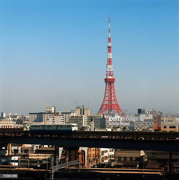An elevated train runs through Tokyo with Tokyo Tower in the background circa 1965