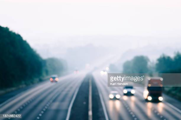 an elevated view of blurred traffic on a uk motorway at dawn - stock photo - driving stock pictures, royalty-free photos & images