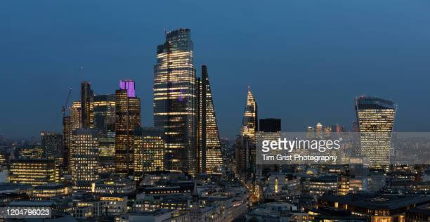 an elevated view of the city of london's illuminated financial district skyline at night - tim grist stock pictures, royalty-free photos & images