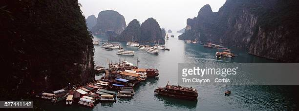 An elevated view of tourist junks visiting Surprise Cave Ha Long Bay Vietnam The bay consists of a dense cluster of 1969 limestone monolithic islands...