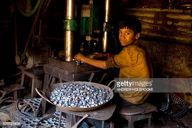 An eleven year old child laborer in a metal parts factory where he works at a metal stamping machine with which he makes rivets Child labor is...