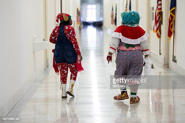 An elf and a clown walk the corridors of the Cannon House Office Building on their way to the 24th annual 'DC Children's Christmas Party on the Hill'...