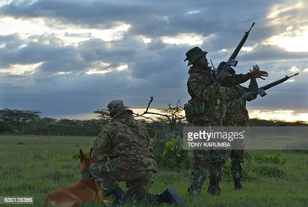 An elite antipoaching unit carries out a weapons check before embarking on an evening patrol on foot on December 5 at the Ol Pejeta conservancy in...