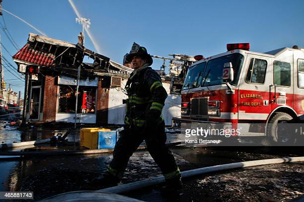 An Elizabeth firefighter works near the burnt remains of business area after a five alarm fire on South Broad Street near Summer Street January 30...