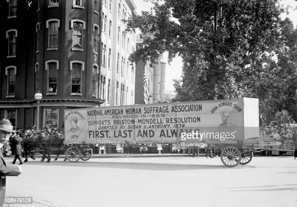 An elongated horsedrawn cart carries a National American Woman Suffrage Association banner through the streets of Washington DC 1914 The...