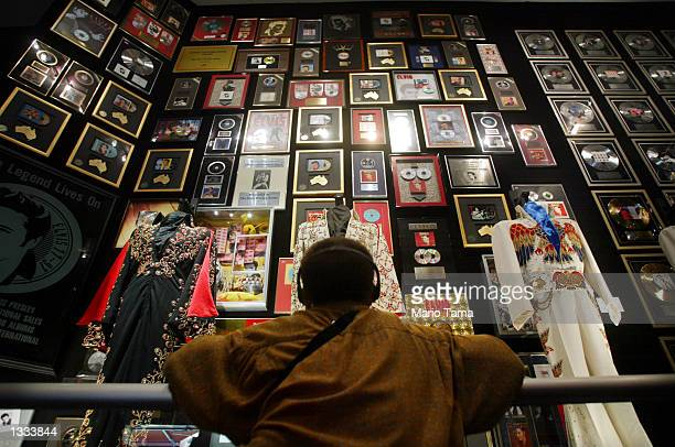 An Elvis fan views Presley memorabilia in the racquetball building at Graceland during Elvis Week on August 12 2002 in Memphis Tennessee 75000 fans...