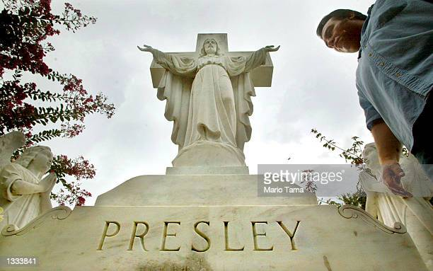 An Elvis fan views the Presley family headstone in the 'Meditation Gardens' area of Graceland where Elvis Presley is buried during Elvis Week on...