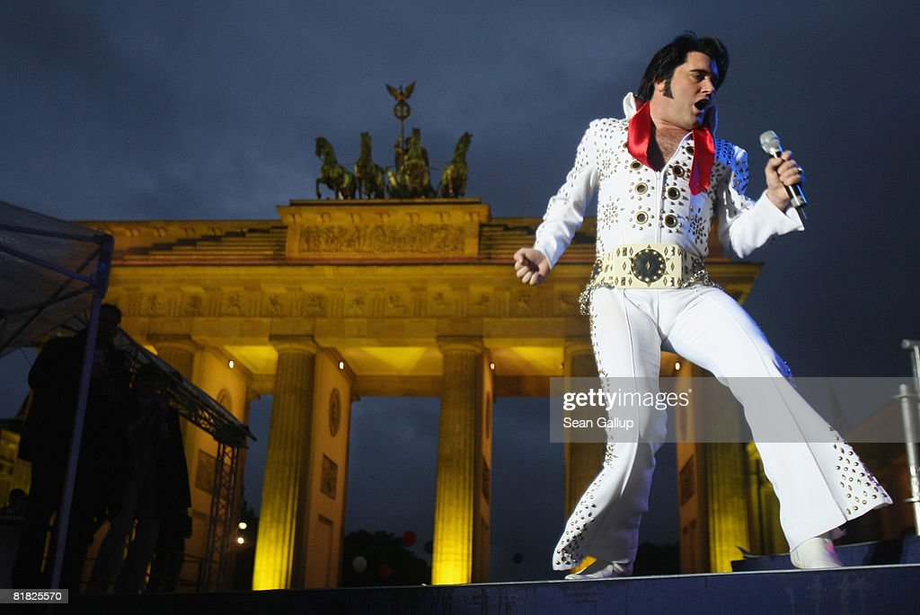 An Elvis Presley impersonator performs at the official opening ceremony and celebration of the new U.S. embassy next to the Brandenburg Gate on July 4, 2008 in Berlin, Germany. Architectural critics claim the embassy, designed by American architect Moore Ruble Yudell, offers little in architectural innovation or design.