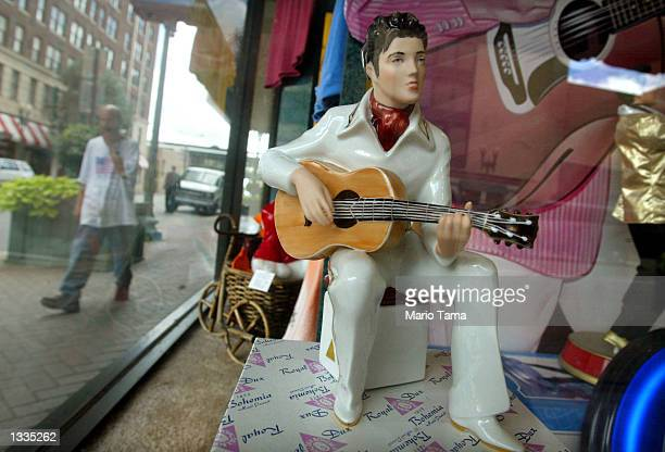 An Elvis Presley souvenir doll is seen in a store window during Elvis Week on August 13 2002 in Memphis Tennessee 75000 fans are expected to attend...
