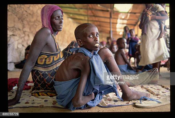 An emaciated boy sits with woman in a relief center during the famine crisis In the 1980s warlord factions joined together to overthrow then...