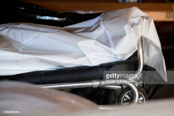 An embalmed body, right, rests in a body bag on a gurney at the Boyd Funeral Home due to a backlog of burials at cemeteries amid a surge of Covid-19...