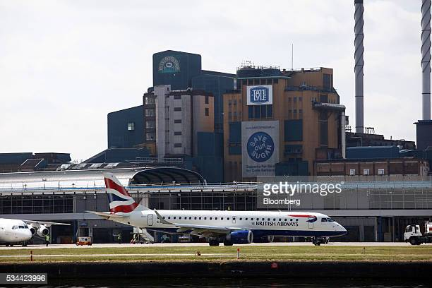 An Embraer SA EJet passenger aircraft operated British Airways a unit of International Consolidated Airlines Group SA taxis against a backdrop of the...