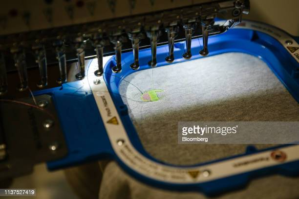 An embroidery machine sews the Champion logo on a sweatshirt at the company's store in Philadelphia Pennsylvania US on Wednesday April 10 2019 The...