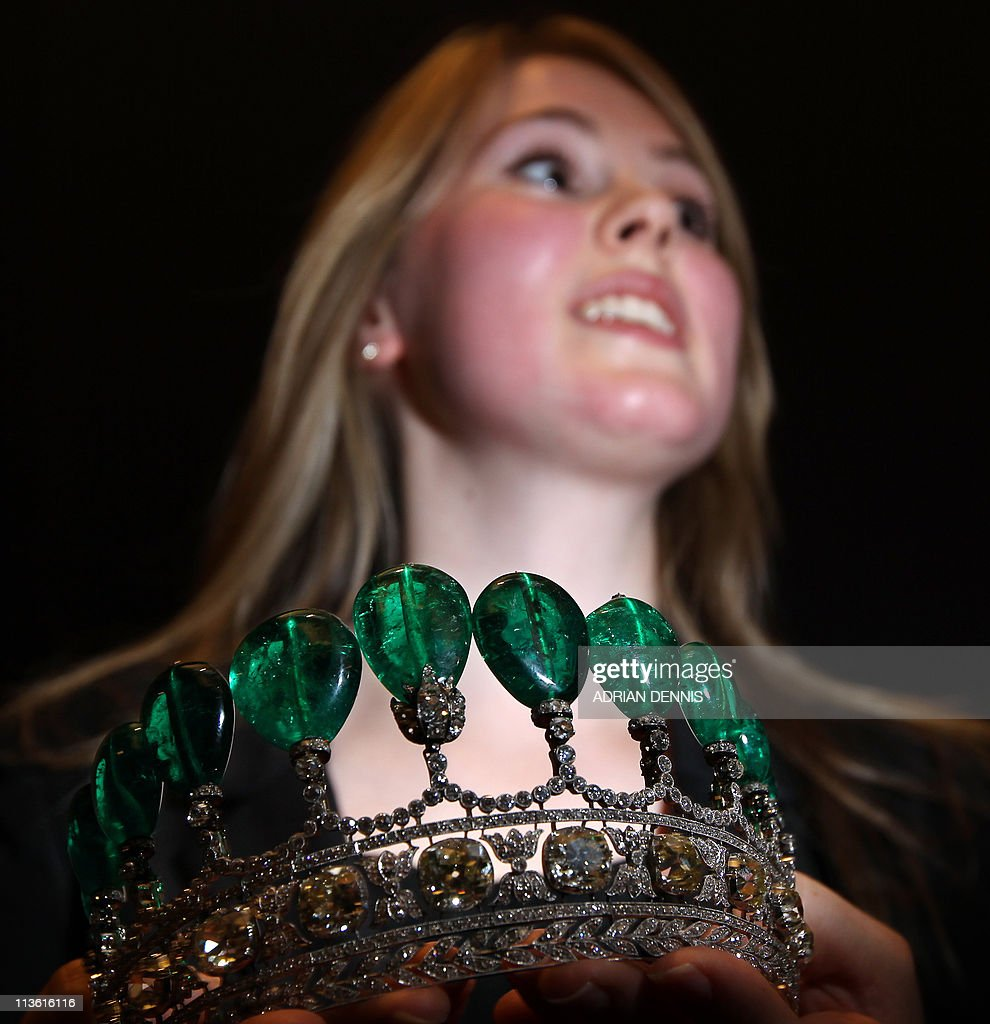 An emerald and diamond tiara is held by : News Photo