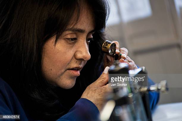 An emerald cutter looks through a magnifying lens at a gemstone she is working on in a cutting and polishing workshop on January 31 2013 in Bogota...