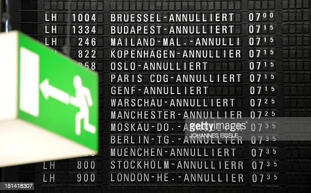An emergency exit sign is seen next to departures board displaying German airline Lufthansa's cancelled flights at the Frankfurt am Main airport, on...