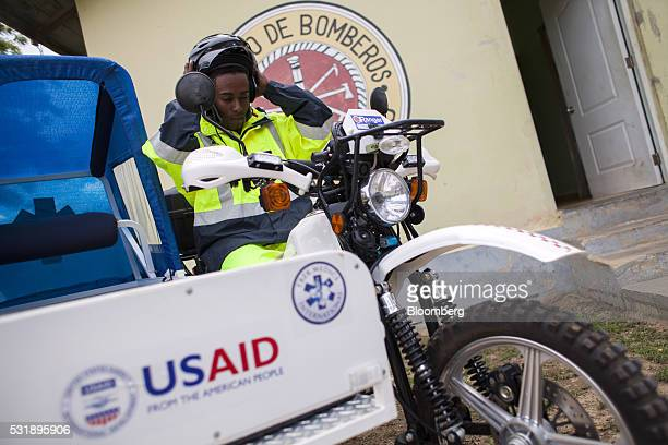 An emergency medical technician puts on a helmet before riding on a USAID donated motorcycle equipped with a sidecar gurney outside of the Manzanillo...