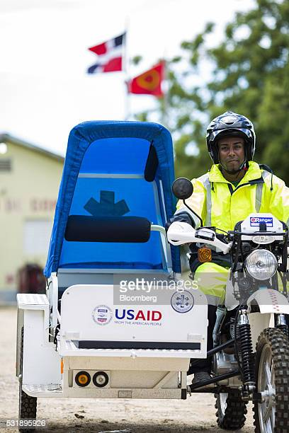 An emergency medical technician sits on a USAID donated motorcycle equipped with a sidecar gurney for a photograph outside of the Manzanillo Fire...