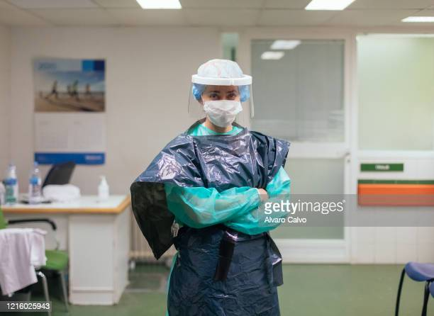 An emergency nurse dressed in garbage bags and a protective mask loaned altruistically by a private company at the emergency entrance door of the San...