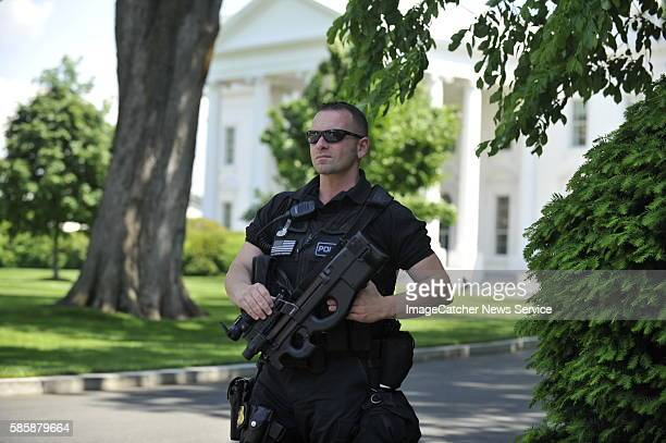 An emergency Response Secret Service Agent looks out at protesters outside of the northwest gate as President Barack Obama aand Vice President Biden...