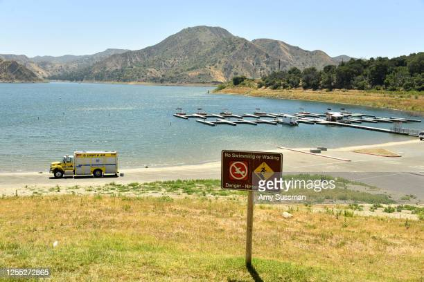 An emergency response vehicle sits in a parking lot near a danger sign warning visitor of hazards for swimming and wading at Lake Piru where actress...