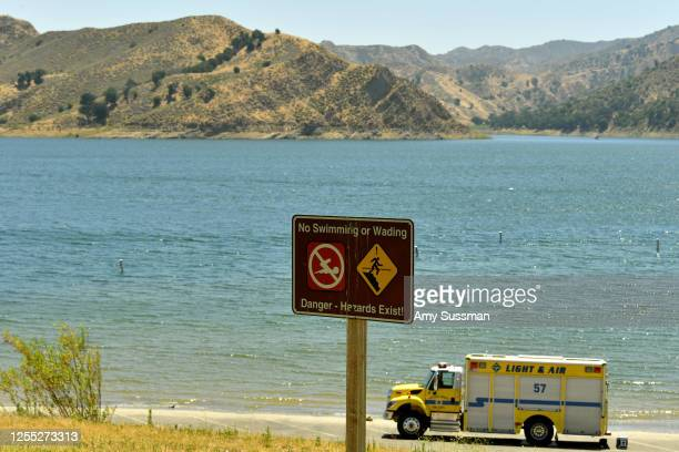 An emergency response vehicle sits in a parking lot near a danger sign warning visitor of hazards for swimming and wading at Lake Piru, where actress...