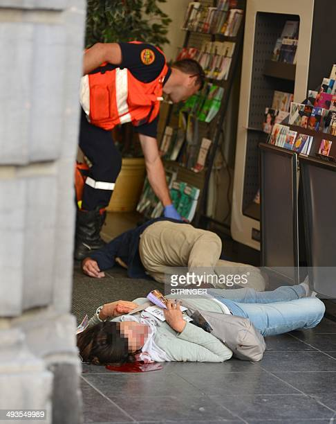 An emergency response worker checks the bodies of two victims of a shooting at a Jewish Museum in Brussels, on May 24, 2014. Three people were killed...