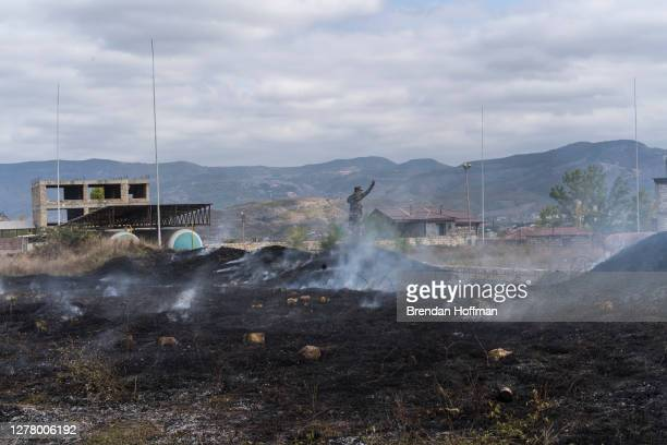 An emergency services member stands atop the site of a grass fire started by a bomb that fell nearby on October 2, 2020 in Stepanakert,...