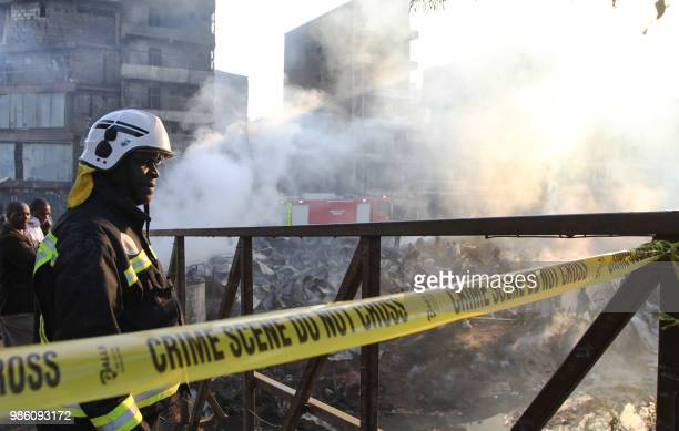 An emergency services personnel looks at the smouldering debris following a fire that gutted the timber dealership at the Gikomba market and nearby...