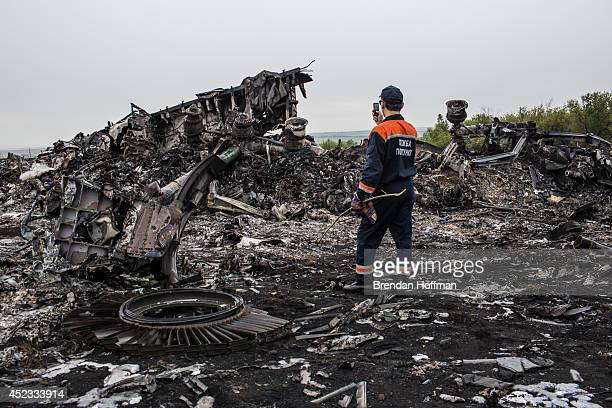 An emergency services worker photographs debris from an Malaysia Airlines plane crash on July 18 2014 in Grabovka Ukraine Malaysia Airlines flight...