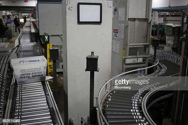 An emergency stop button stands between two conveyor belts for an automated mail sorting machine at the United States Postal Service sorting center...