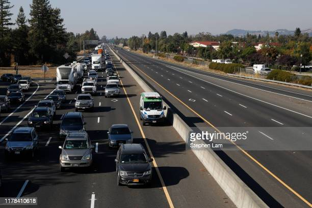 An emergency vehicle drives on a shoulder along Highway 101 as motorists evacuate nearby towns and cities in anticipation of the expected wind event...