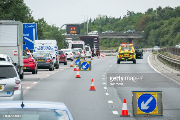 An emergency vehicle traffic officer from Highways England diverting the traffic on the motorway M11 heading to London after an accident that created...