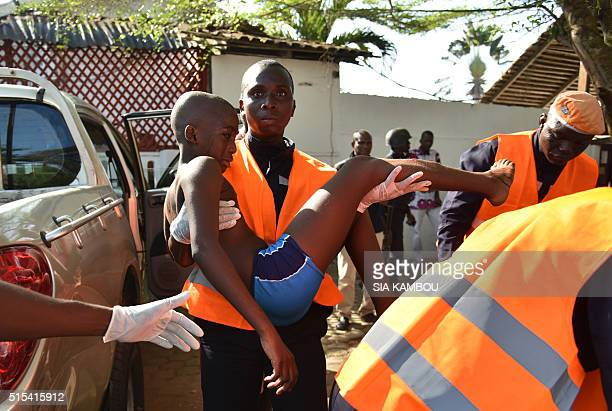 TOPSHOT An emergency worker carries a young boy who was injured during an attack on the beach at the hotel Etoile du Sud in Grand Bassam on March 13...