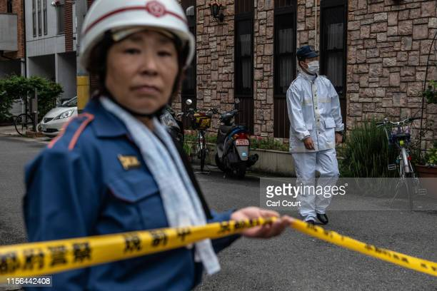 An emergency worker holds a cordon ribbon as a police officer walks past near the Kyoto Animation Co studio building after an arson attack, on July...