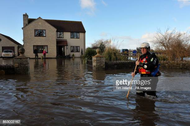 An emergency worker walks down the road outside a property in Moorland Somerset after residents were advised to evacuate after flood defences were...