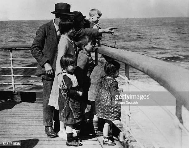 An emigrant family sights their destination Canada from the ship deck