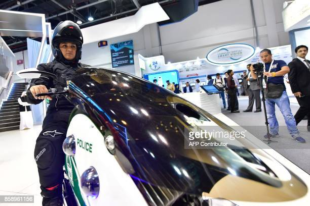 An Emiratee police officer shows a motorbike at the Gitex 2017 exhibition at the Dubai World Trade Center in Dubai on October 8 2017 / AFP PHOTO /...