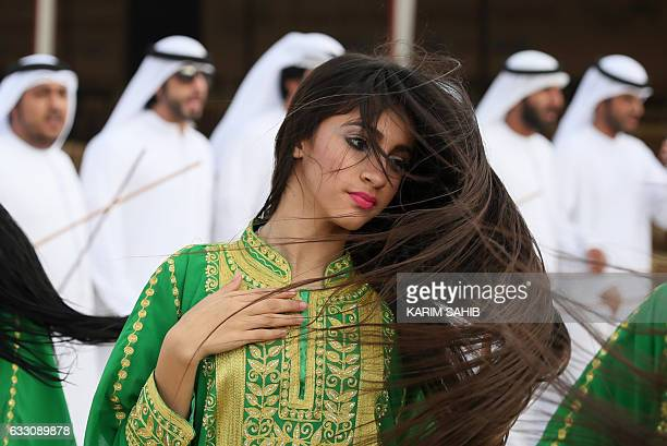 An Emiratee woman performs a traditional dance during the camel festival at the Sweihan racecourse in AlAin on the outskirts of Abu Dhabi on January...