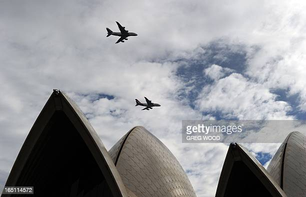 An Emirates A380 aircraft and a Qantas A380 aircraft fly over the Sydney Opera House on March 31 2013 to mark the official launch of the partnership...