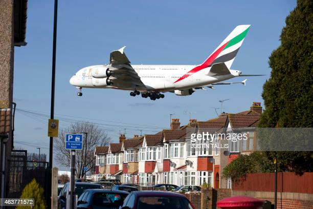 An Emirates Airbus A380 aircraft flies over a house as it comes into lane at Heathrow Airport in west London on February 18 2015 AFP PHOTO / JUSTIN...