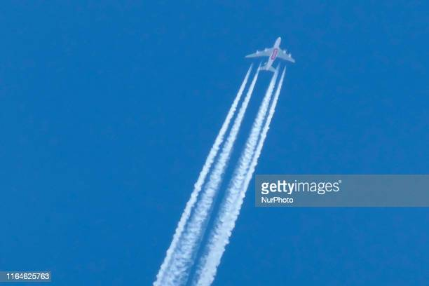 An Emirates Airbus A380 aircraft overfly London England UK in the summer blue sky as seen from London city center on 1st August 2019 The doubledecker...