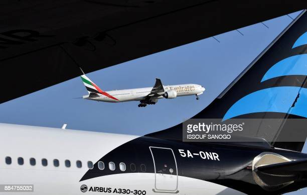 An Emirates Airline Boeing 777 aircraft is seen next to an Airbus A330300 as it takes off from the Felix HouphouetBoigny Airport in Abidjan on...