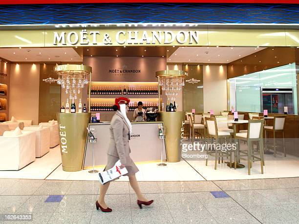 An Emirates Airline employee walks past the Moet and Chandon champagne bar inside terminal 3 at concourse A the new A380 terminal at Dubai...