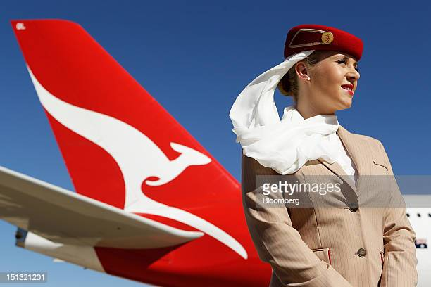 An Emirates Airline flight attendant stands in front of a Qantas Airways Ltd aircraft during a media event in Sydney Australia on Thursday Sept 6...