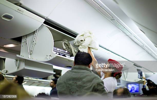 An Emirates Airline stewardess airline helps a businessman with his special handluggage suitcase to lift it up into the baggage compartement on...