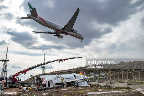 An Emirates Airlines airplane prepate to landing as workers remove the wreckage of the Pegasus Airlines Boeing 737 airplane in Istanbul, on February...