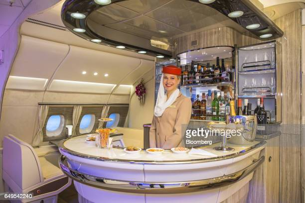 An Emirates Airlines cabin crew attendant stands in the new bar area for the Airbus A380 aircraft during the unveiling at the ITB Travel Fair in...