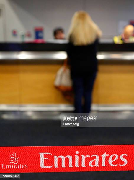 An Emirates logo sits on a a barrier as a passenger speaks with staff at a boarding desk inside Terminal 3 of Heathrow Airport in London UK on...