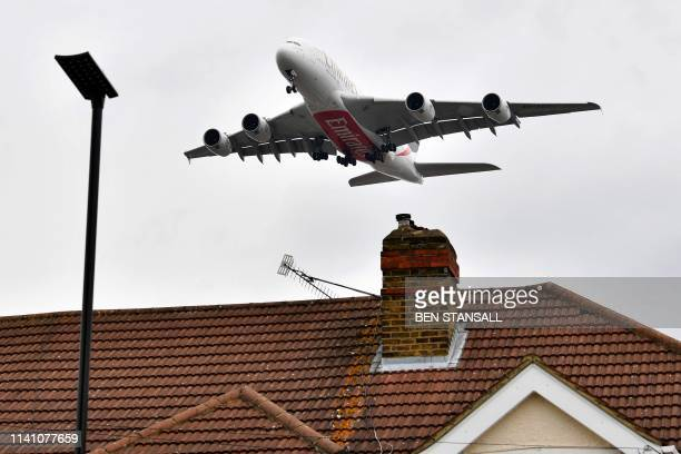 An Emirates operated Airbus A380800 doubledecker aircraft flies over residential houses and properties as it prepares to land at London Heathrow...
